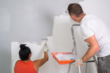 Couple painting a room with paint rollers - 217275571