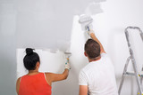 Couple painting a room with paint rollers - 217275594