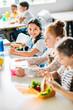 Leinwanddruck Bild - little happy schoolgirls taking lunch at school cafeteria