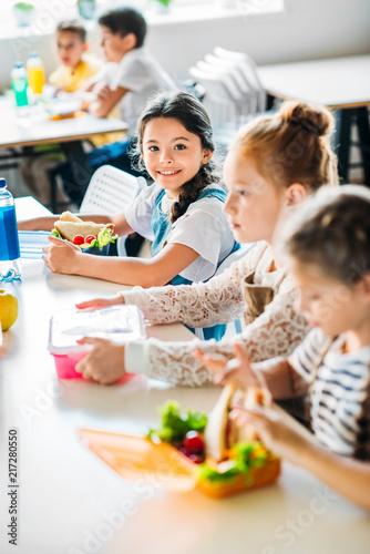 Leinwanddruck Bild little happy schoolgirls taking lunch at school cafeteria