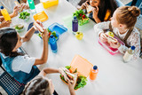 high angle view of group of schoolgirls taking lunch at school cafeteria - 217280702