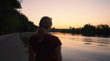 Young woman walking by the river at sunset - 217319110
