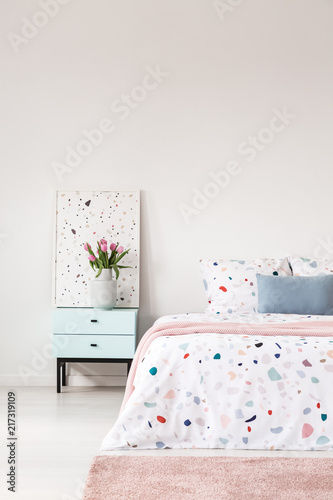 Cropped Photo Of A Bed With Lastrico Sheets, Pink Rug And Bedside Table  With A