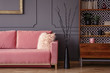 Pink sofa next to black decor and wooden cabinet in vintage living room interior. Real photo