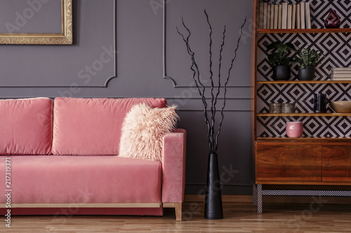 Różowa kanapa obok czarnego wystroju i drewnianej szafki w rocznika żywym pokoju wnętrzu. Prawdziwe zdjęcie