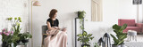 Young woman covered with blanket sitting on armchair and reading a book in white apartment interior with many fresh plants - 217319579