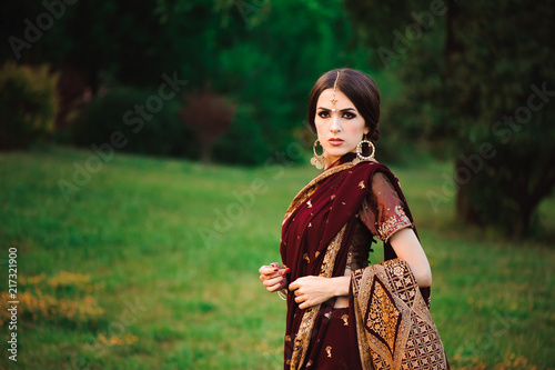 Foto Murales Beautiful Arabian woman portrait. Young Hindu woman with mehndi tattoos from black henna on her hands.