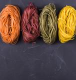 Raw colored tagliatelle and spaghetti