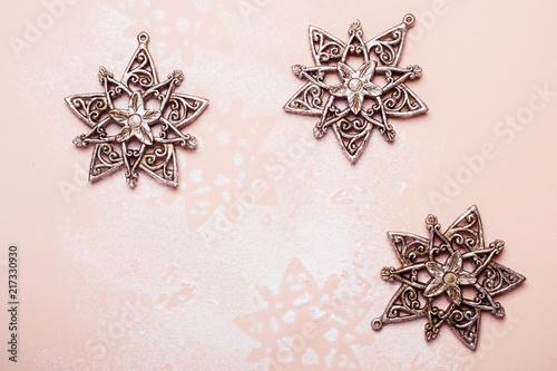 Vintage srebrne zabawki świąteczne płatki śniegu na różowym tle