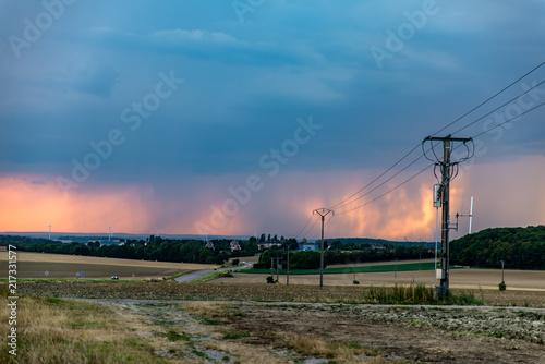 Aluminium Blauwe jeans Paysage de campagne au crépuscule orange, l'orage se prépare à éclater, la pluie au loin lazarde le ciel au dessus de l'horizon et des éoliennes