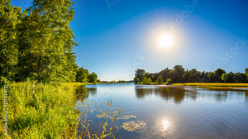 Leinwanddruck Bild Summer landscape with trees, meadows, river and bright sun