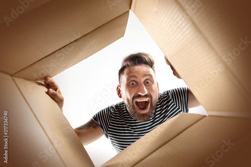 Leinwanddruck Bild The surprised man unpacking, opening carton box and looking inside. The package, delivery, surprise, gift lifestyle concept. Human emotions and facial expressions concepts