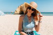 Quadro Young attractive woman wearing stylish straw and sunglasses hat sitting and relaxing under the sun on the beach.