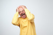Mature man in yellow tshirt suffering from loud music and pain screaming trying to plug ears against grey background.