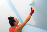 Woman at painting a room with paint roller - 217364902