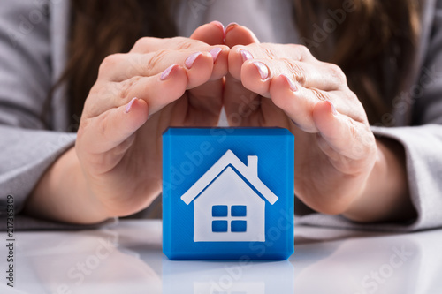 Foto Murales Woman Protecting Cubic Block With House Icon