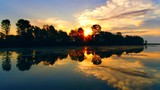 Moving down tranquil river at sunrise with beautiful reflections in water.  - 217365725