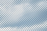 close up on iron chainlink fence against sky - 217383758