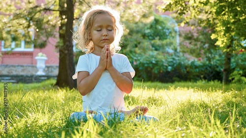 Plakat Little cute baby girl meditates on the grass at green summer park.