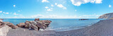 Panorama view of Kamari Beach with breakwater of rocks in the sea, Santorini, Greece