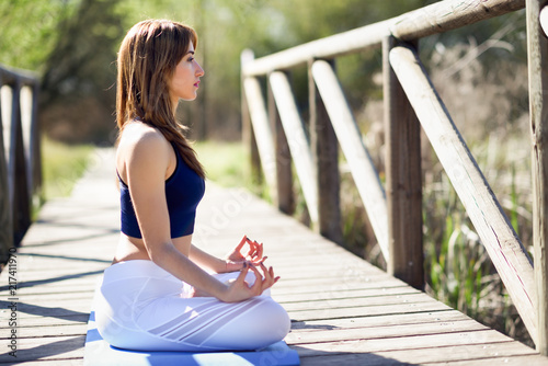 Sticker Young beautiful woman doing yoga in nature