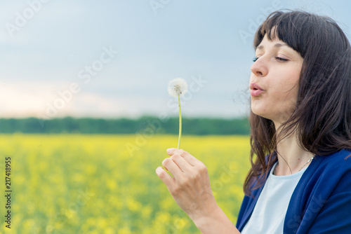 young emotional beautiful sensual pretty girl in a white shoe and in a blue cape top, with dark hair on the yellow yellow reed field with a dandelion in his hands - 217418955