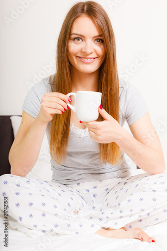 Wall mural Smiling woman holding cup of drink in bed