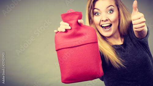 Foto Murales Happy woman holds hot water bottle