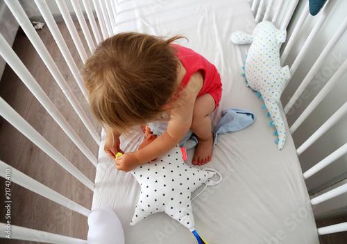 Leinwanddruck Bild baby girl playing in bedroom