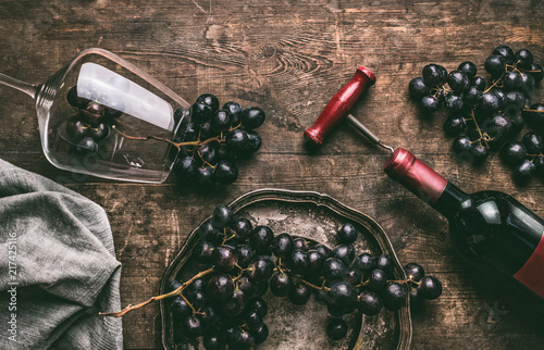 Red wine still life. Wine Glass with  bottle, corkscrew and red grape clusters on wooden rustic background, top view