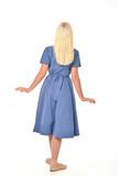 full length portrait of blonde girl wearing blue dress. standing pose with back to the camera. isolated on white  studio background.