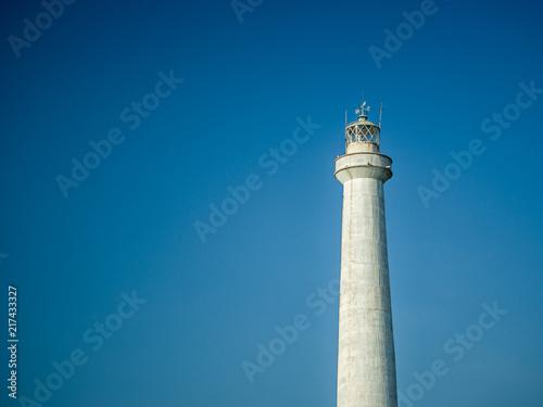 Aluminium Vuurtoren A white lighthouse set against a blue sky in the summer