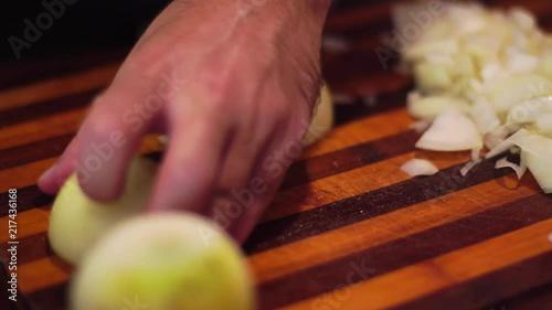 Poster man cuts onions on a cutting board