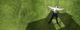 Pensive businessman on grass - 217454357