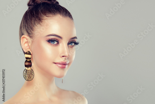Leinwanddruck Bild Beautiful model girl with pink manicure on nails . Fashion makeup and cosmetics . Big golden shine  earrings jewelry .