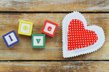 Wooden blocks with letters love and red knitted heart