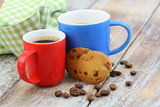 Two colorful mugs of black coffee on rustic wooden surface with biscuits and coffee beans scattered around