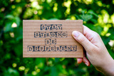 Woman hand holding cardboard card with words Stay Strong Be Different against green nature background. - 217468347