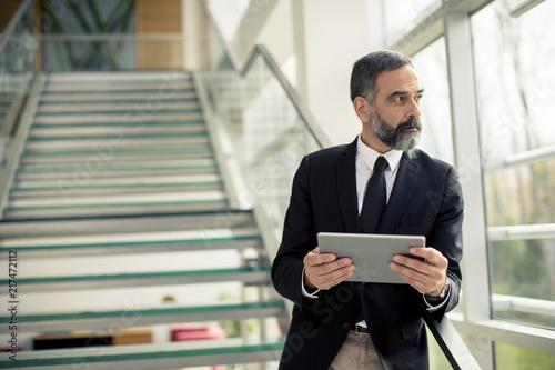 Sticker Handsome senior businessman with digital tablet in the modren office