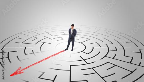 Leinwanddruck Bild Businessman going through the maze with red arrow
