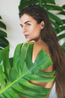Leinwanddruck Bild - Portrait of young and beautiful woman with perfect smooth skin in tropical leaves