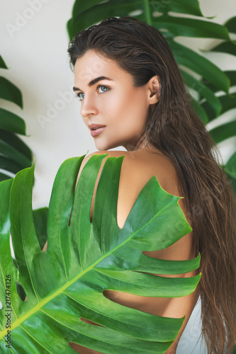 Leinwanddruck Bild Portrait of young and beautiful woman with perfect smooth skin in tropical leaves