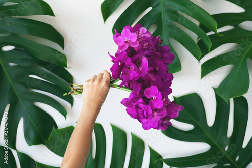 Foto Murales Female hand with a bunch of orchid flowers