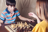 Mother and son are playing chess at home. Mother is thinking over her move and son is concentrated on the process.