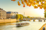 bridge Pont Neuf and Seine river with floating ship at sunny autumn sunset, Paris, France, toned