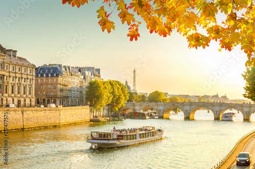 Wall mural bridge Pont Neuf and Seine river with floating ship at sunny autumn sunset, Paris, France, toned