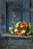 Bunter Blumenstrauß auf einem alten Gartenstuhl