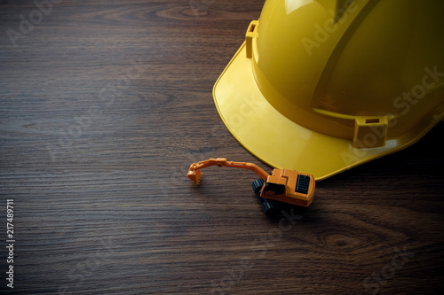 Foto Murales tracked excavator construction machine with yellow safety helmet on wood background