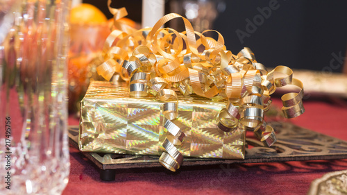 Gift wrapped box with curly ribbons on a holiday table. - 217495756