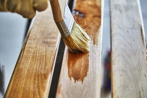 Paint Brush in a can of varnish in preparation to stain the wood slats - 217505707